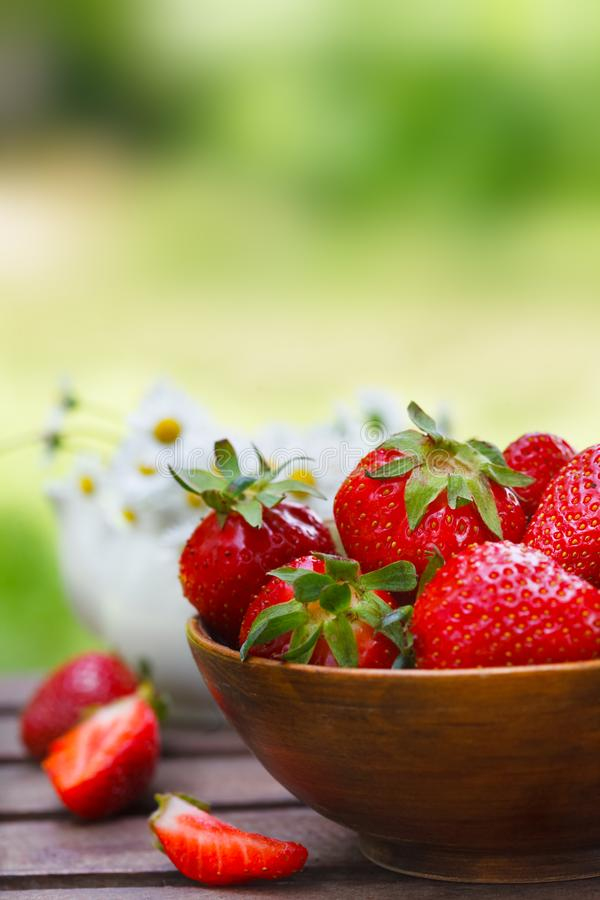 Fresh strawberries in a bowl on wooden table royalty free stock image