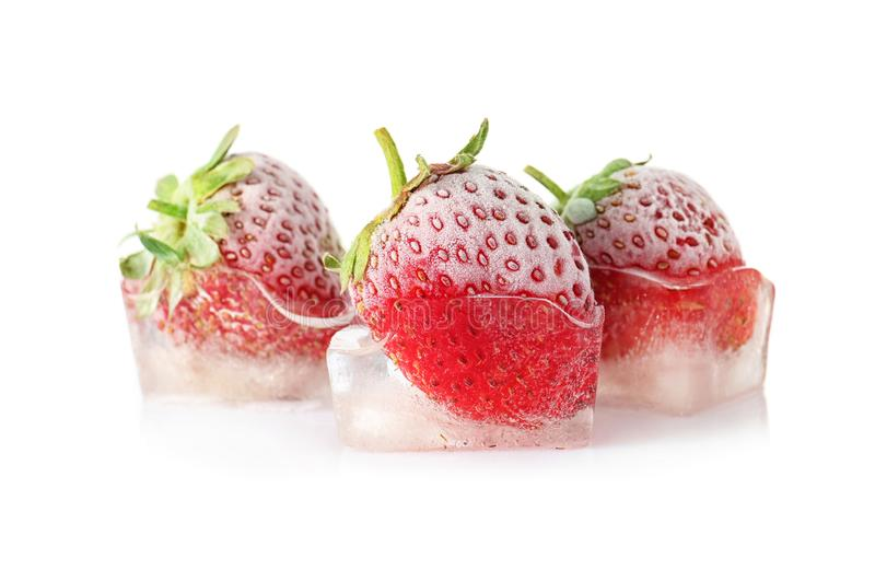 Fresh strawberries frozen in ice cubes royalty free stock photography