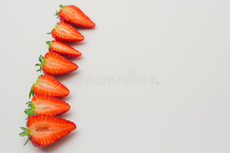 Fresh strawberries halved and arranged on a white background. stock image