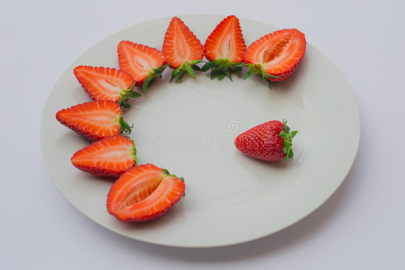 Fresh strawberries halved and decorated on a white plate. stock photo