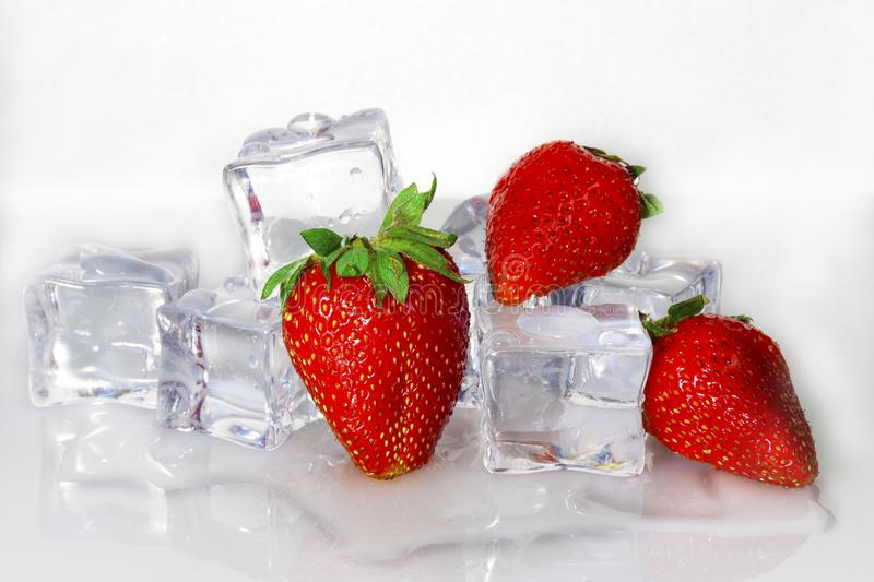 Fresh strawberries with ice cubes on a light background royalty free stock photography