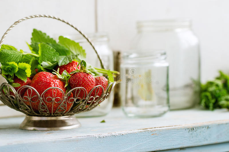 Fresh strawberries and melissa herbs stock images