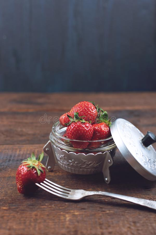 Fresh strawberries in metal plate and one berry on fork still life on dark wooden background. Organic garden strawberry on rustic royalty free stock images