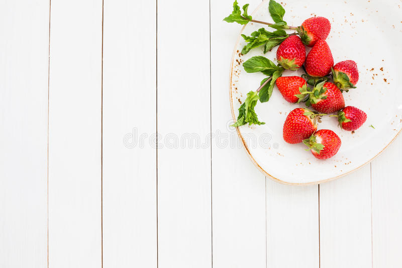 Fresh strawberries with mint in plate on white wooden table. Top view royalty free stock photo