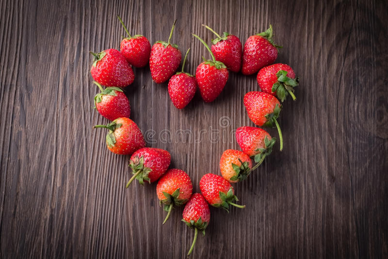 Fresh strawberries on old wooden background stock images