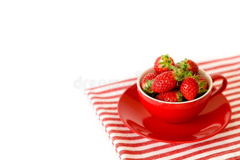 Fresh strawberries in a red bowl on white background. Horizontal stock photography