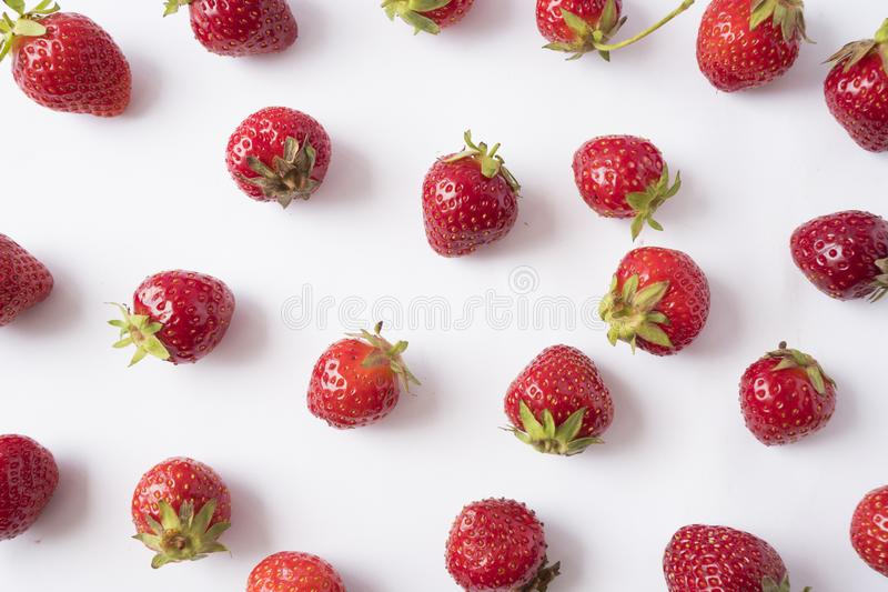 Fresh strawberries scattered on white background. Strawberries on a white background. Fruits with copy space for text. Top view. royalty free stock images