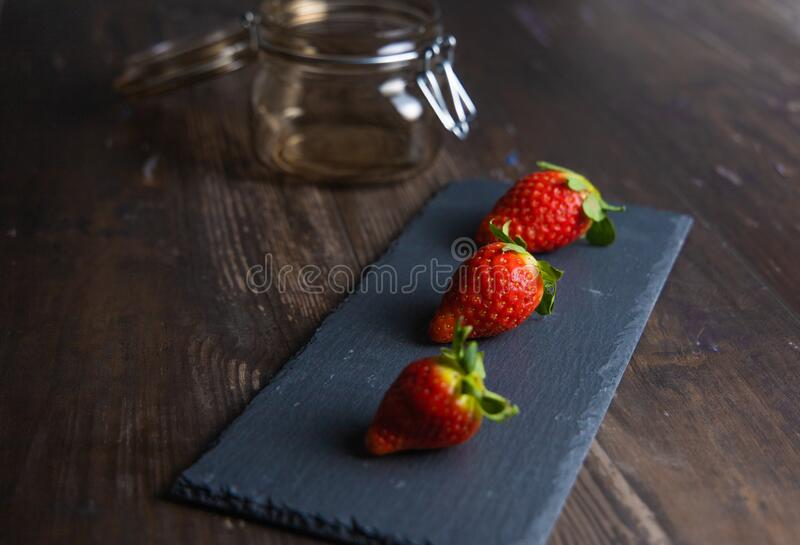 Fresh strawberries still life on slate plate with glass jar and stale base.  royalty free stock photography