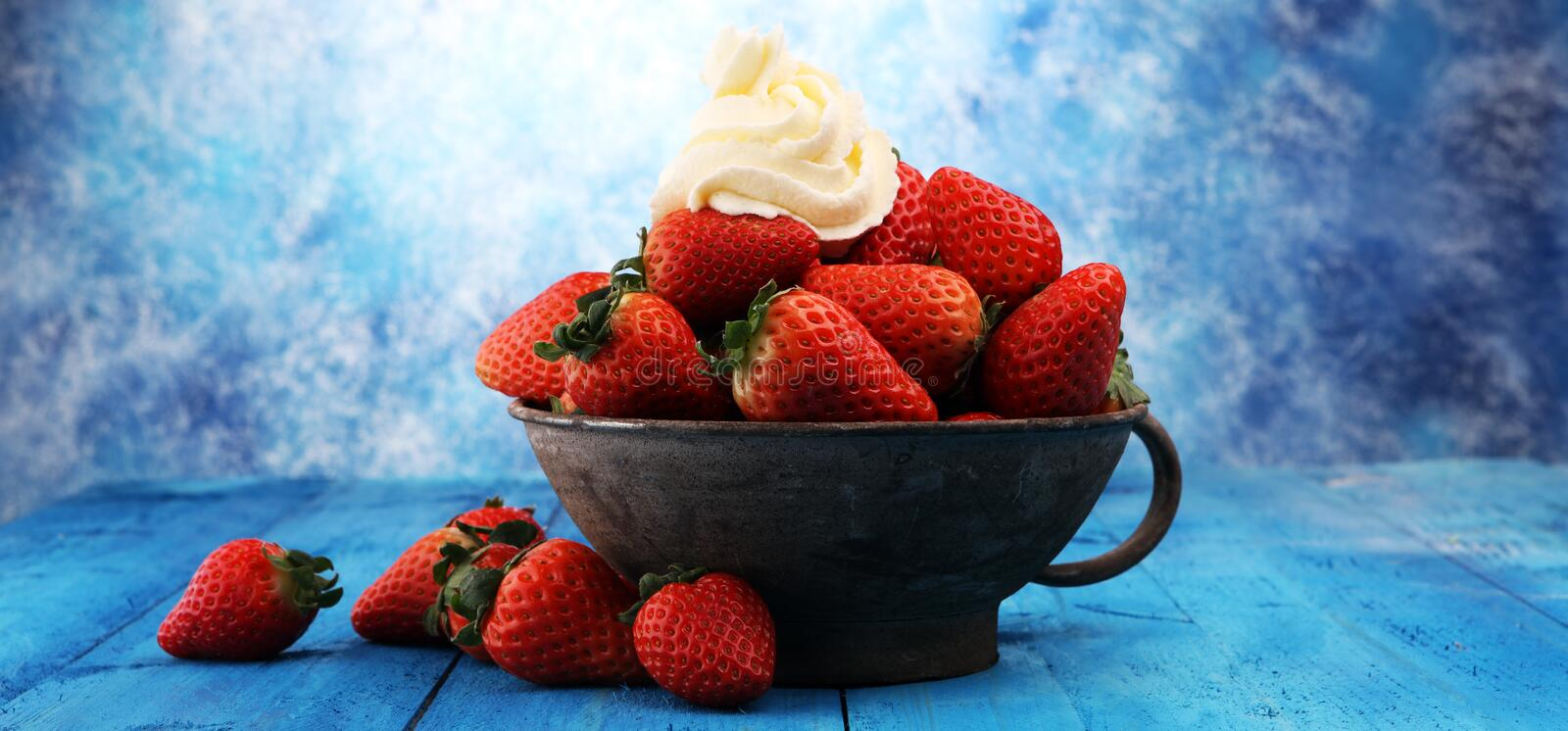 Fresh strawberries and whipped cream on grey vintage bowl. royalty free stock photography