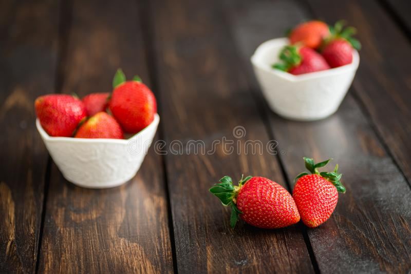 Fresh strawberries in white bowl on old wooden table royalty free stock photo