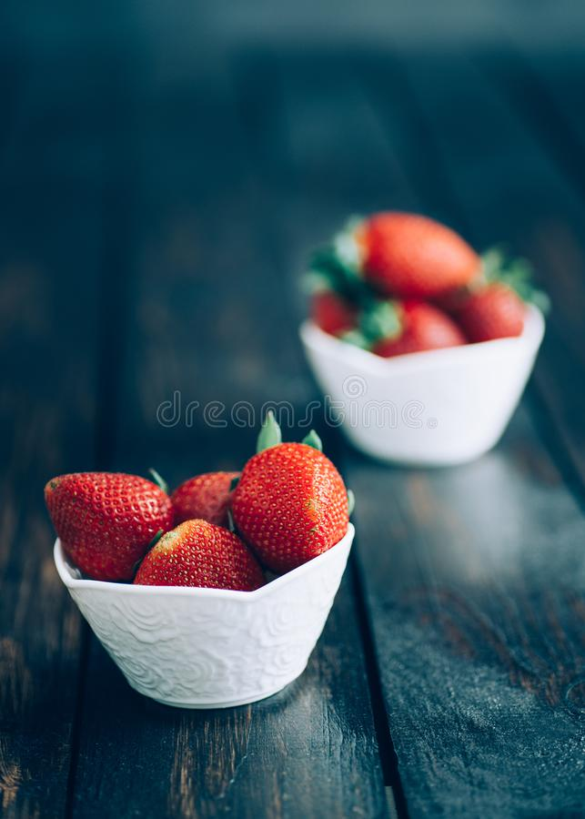 Fresh strawberries in white bowl on old wooden table royalty free stock images