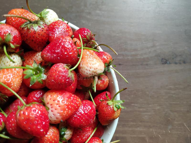 Fresh strawberries are in the white bowl on wooden table. stock image