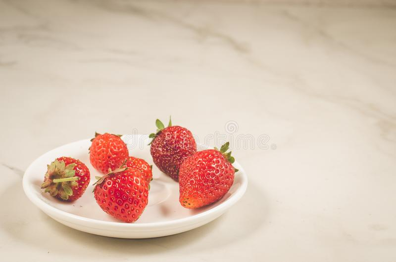 Fresh strawberry berries in a bowl/fresh strawberry berries in a bowl on a white marble background, copy space and selective focus. Strawberries red fruit ripe stock image