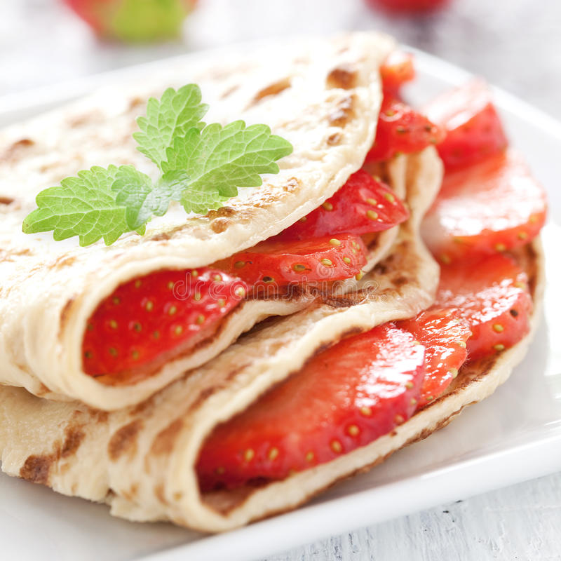 Fresh strawberry crepe. Fresh crepe with strawberries with mint on a plate stock images