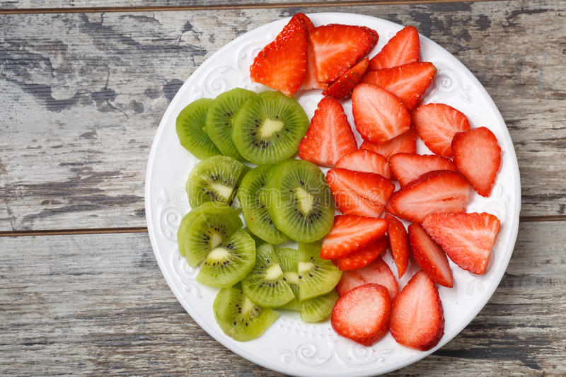 Fresh strawberry and kiwi slices on cutting plate.  stock image