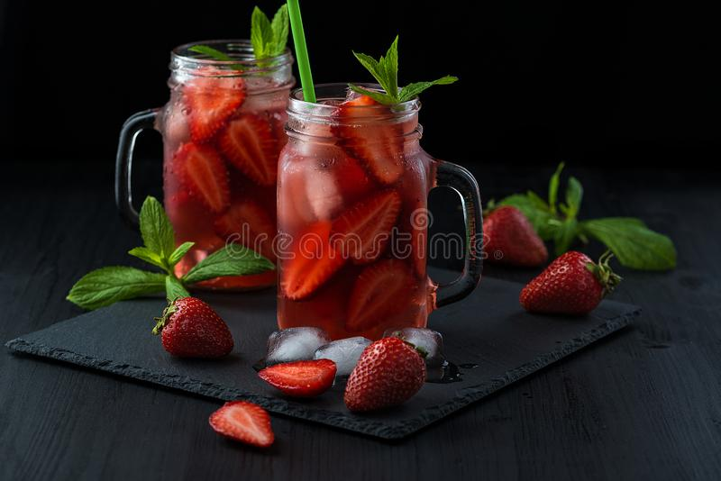 Fresh strawberry smoothie. Fresh summer cocktail with strawberries and ice cubes on a dark background on a black wooden table stock photography