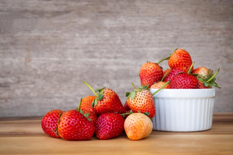 Fresh strawberry in white small bowl on wooden table. Healthy and sweet fruit royalty free stock photo