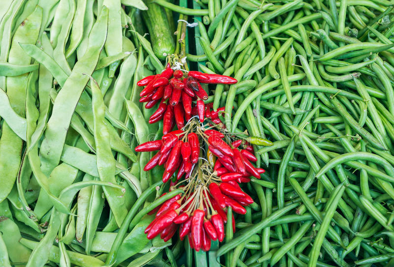 Fresh string beans and red chili peppers on a market stall royalty free stock photo