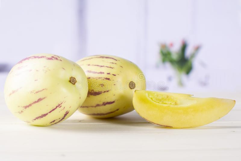 Fresh striped pepino melon with red tulips royalty free stock photos