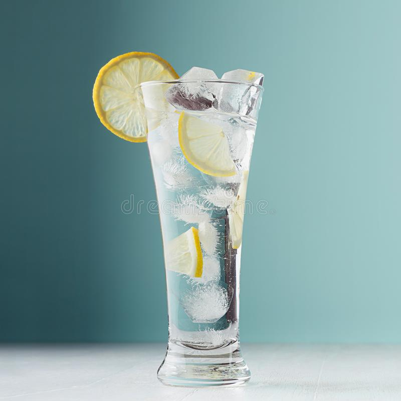 Fresh summer citrus cold drink with yellow lemon pieces, ice cubes, tonic in light soft pastel  blue background on white wood. stock photography