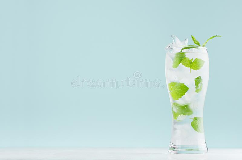 Fresh summer cold mint drink with green leaf, ice cubes, tonic in light soft pastel  blue color background on white wood board. stock photos