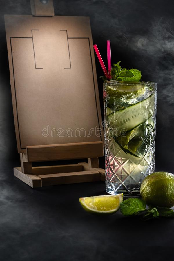 Fresh summer cucumber lemonade with two pink straws in the glass. Wooden Menu Holder with copy space on the black background with stock photos
