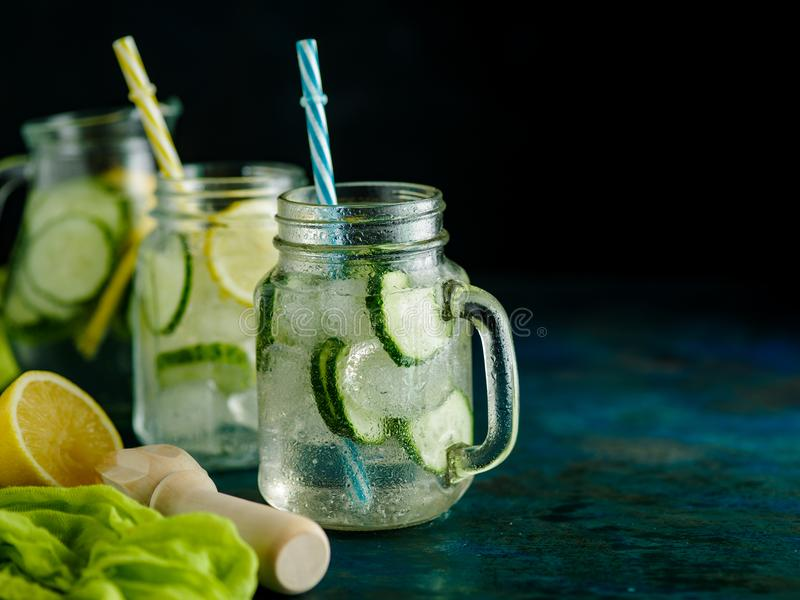 Fresh Summer Drink. Healthy detox fizzy water with lemon and cucumber in mason jar over dark background. Healthy food concept. De royalty free stock photo