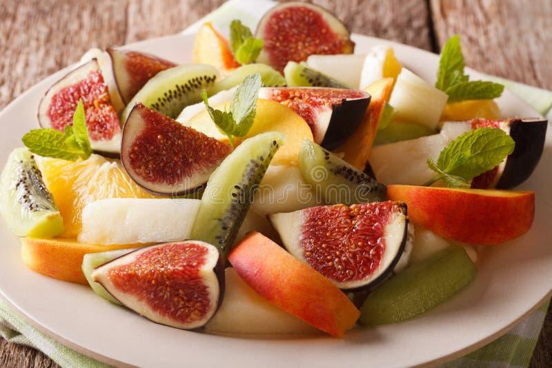 Fresh summer fruit salad with fig, peach, melon, kiwi and orange royalty free stock image