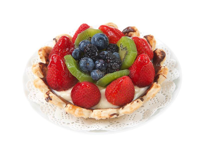 Fresh fruit tart on a plate on white background royalty free stock images