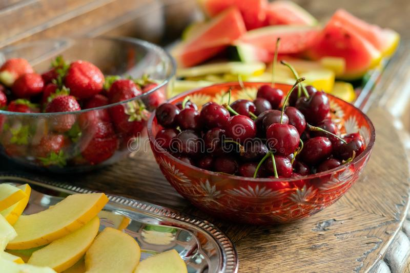 Fresh summer fruits: cherries, organic strawberries, melon slices, water melon in vintage crystal bowl on old wooden table royalty free stock images