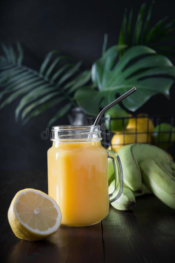 Fresh summer fruits juice with banana, lemon on dark tropical background. Close up. Summer drink royalty free stock photo