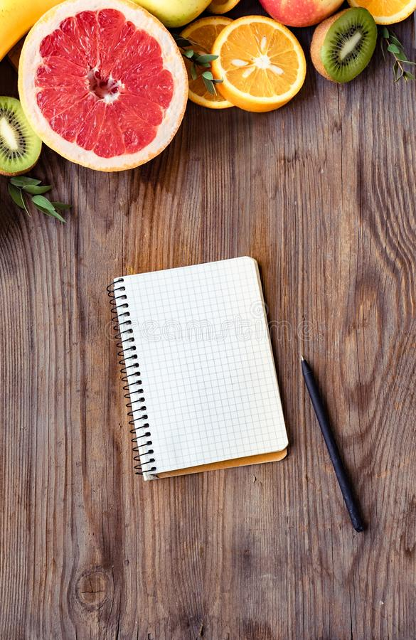 Fresh summer fruits and notebook on brown wooden background, top vertical view stock images