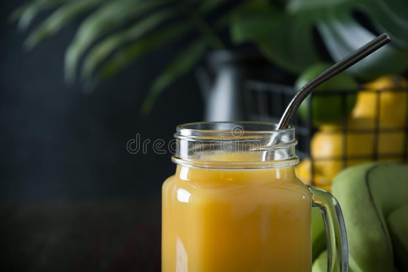 Fresh summer fruits smoothies with banana, lime on dark tropical wooden table. Space for text. Close up. Fresh summer fruits smoothies or juice with banana, lime stock photography