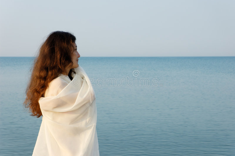 Fresh summer morning. Beautiful young woman on the sea shore in the morning taking the air stock image