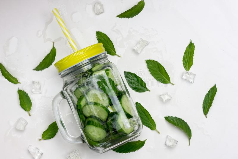 Fresh summer organic lemonade drink with slices cucumber, ice, mint, in a glass jar with a yellow lid and straw on a stock photos