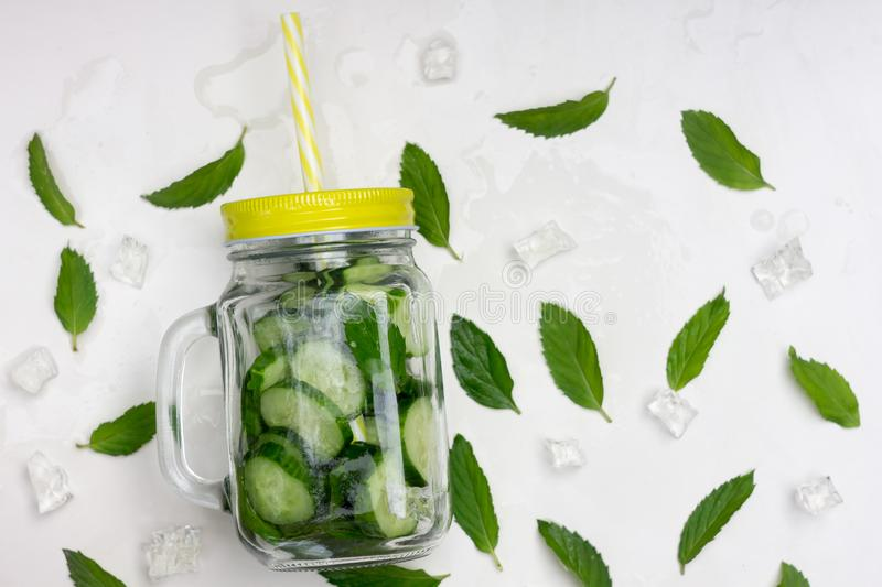 Fresh summer organic lemonade drink with slices cucumber, ice, mint, in a glass jar with a yellow lid and straw stock photos