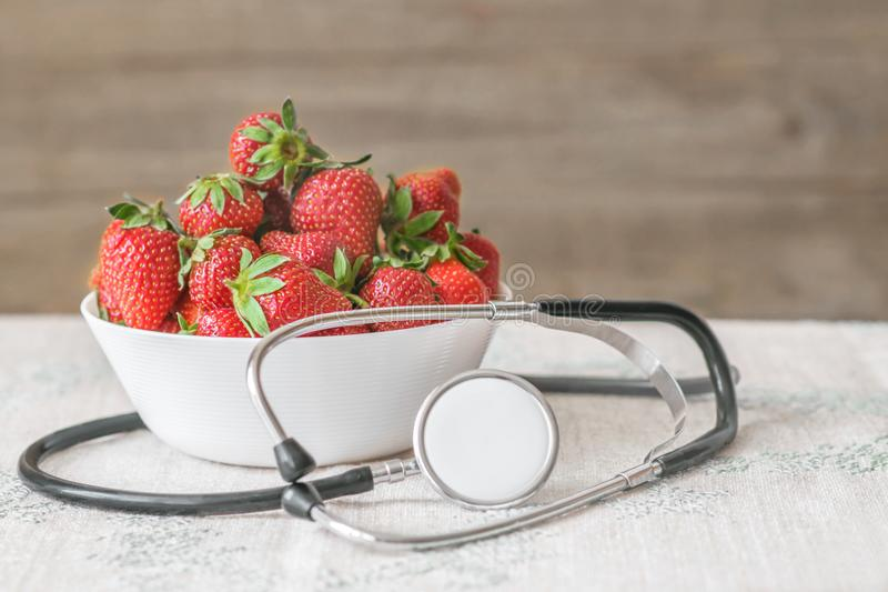 Fresh summer red strawberries in a white cap with medical stethoscope around on table. The concept of healthy environmentally-clea royalty free stock photos