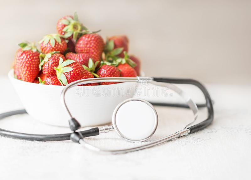 Fresh summer red strawberries in a white cap with medical stethoscope around on table on light background. The concept of healthy stock photos
