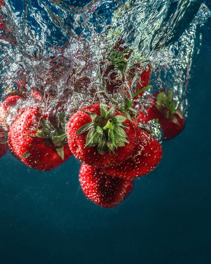 Fresh summer strawberries. Strawberries in water. spray, berries, red and blue. still-life. background. abstraction. food. photo of food. Strawberry berries royalty free stock photos