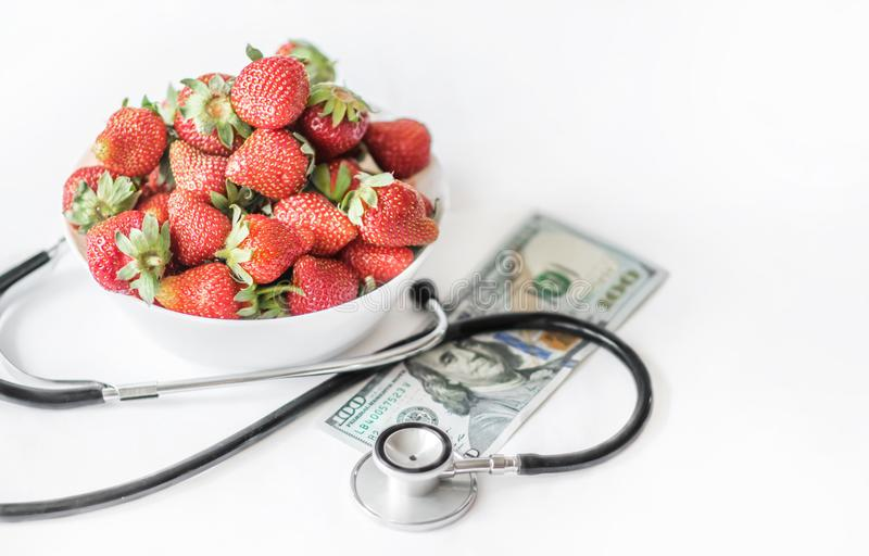 Fresh summer strawberries on a white background with medical stethoscope and monye banknote one hundred dollars. The concept of he royalty free stock photo
