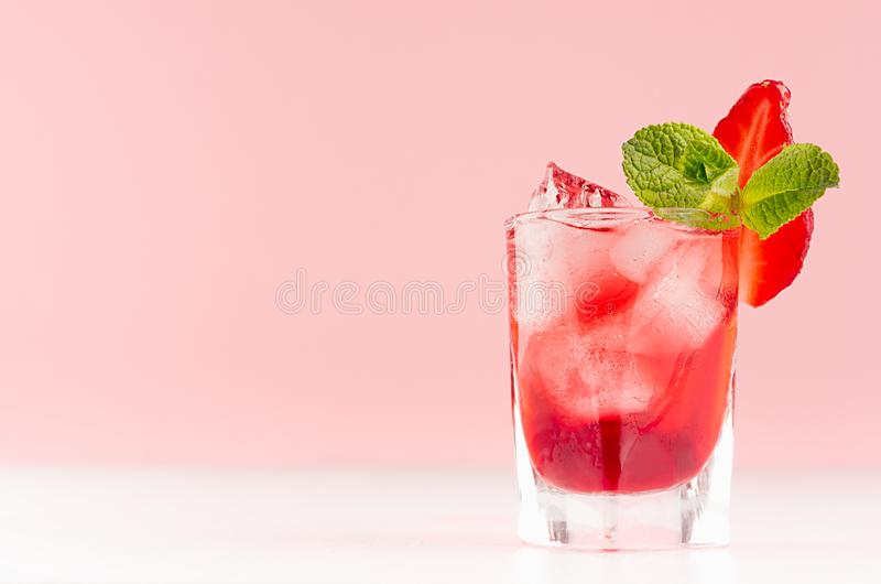 Fresh summer strawberry homemade cocktail in shot glass with ice cubes, strawberry slice, green mint in elegant pastel pink color. royalty free stock photos