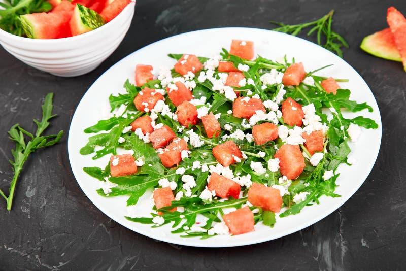 Fresh summer watermelon salad with feta cheese and arugula stock photo