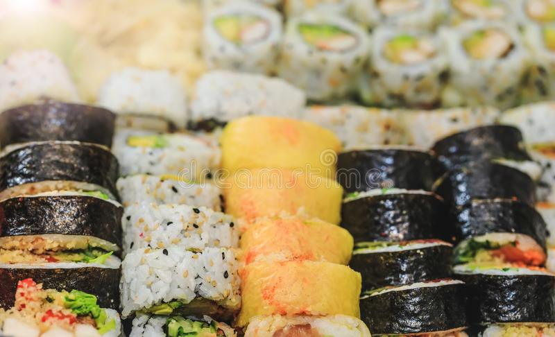 Fresh sushi rolls with salmon, avocado, tuna and cucumber. Maki plate with rice and nori. Delicious Japanese food with sushi roll stock image