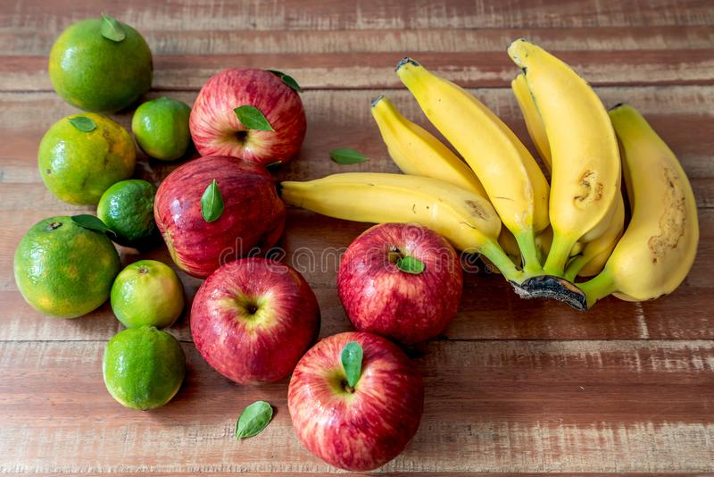 Colorful fresh bananas, lemons, oranges and apples on wooden background stock photo
