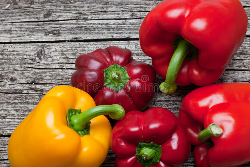 Fresh sweet bell peppers on rustic wood stock photo