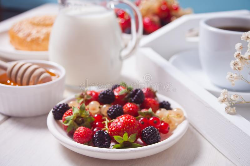 Fresh sweet berries on the white plate, bagel, cup of coffee and honey for breakfast royalty free stock photos
