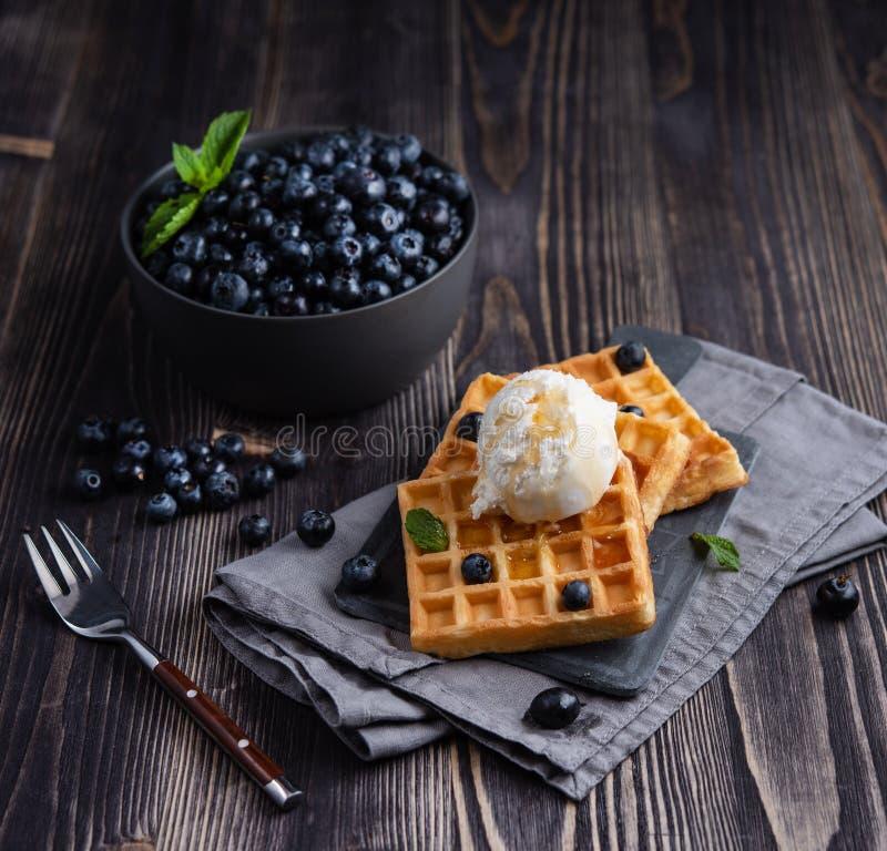 Fresh sweet blueberry with aromatic belgian waffels vanilla ice cream and honey dark wood table. Rustic stock image