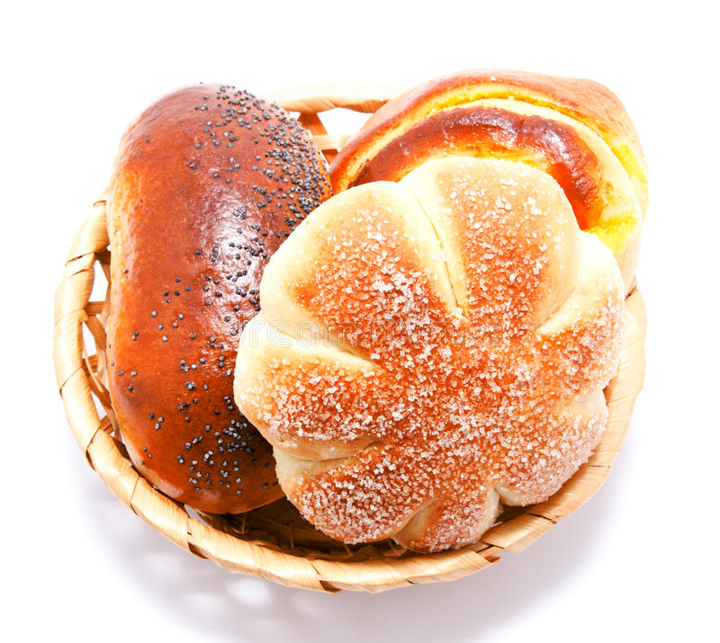 Fresh sweet buns and rolls with poppy and cream in the basket. Isolated on a white royalty free stock photo