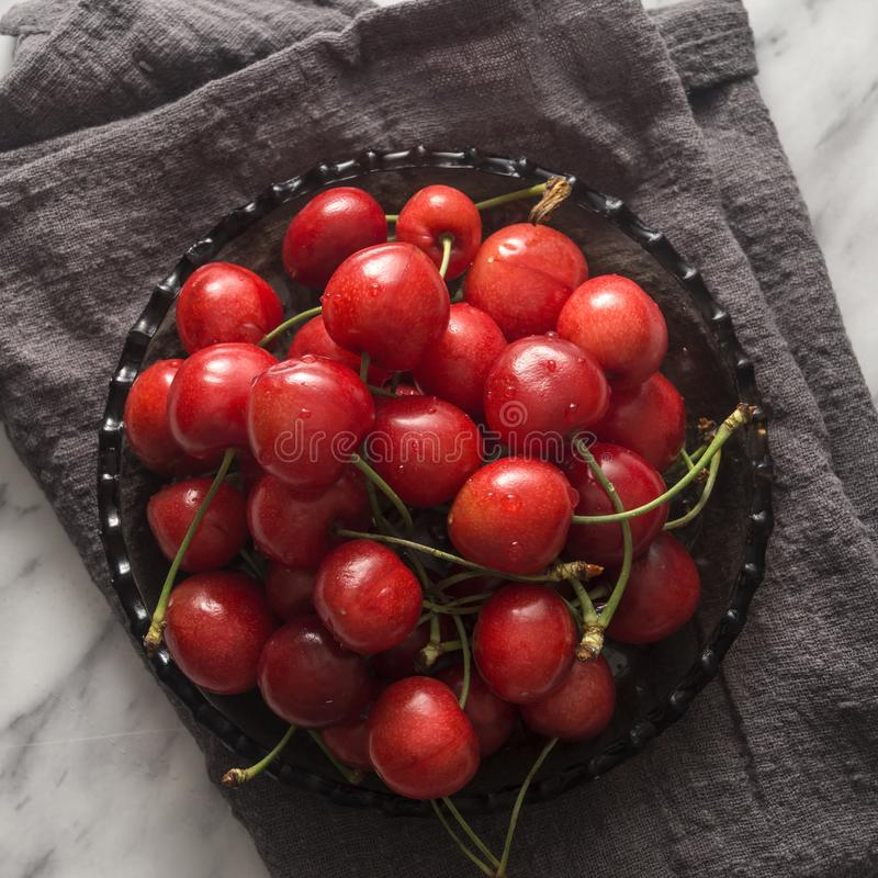 Fresh sweet cherries bowl with water drops on the table. Top view royalty free stock image