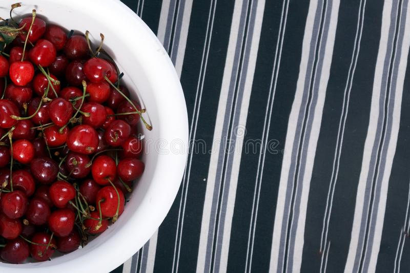 Fresh sweet cherry in a white cup on a striped background royalty free stock photo